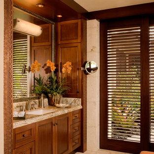 Immagine di una stanza da bagno tropicale con lavabo sottopiano, ante in legno bruno, piastrelle beige e ante con riquadro incassato
