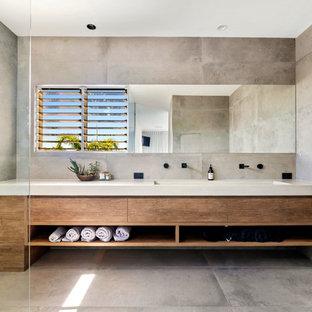 Foto de cuarto de baño actual con baldosas y/o azulejos grises, lavabo de seno grande, encimera de cemento, puertas de armario de madera oscura, paredes grises, suelo gris y encimeras grises