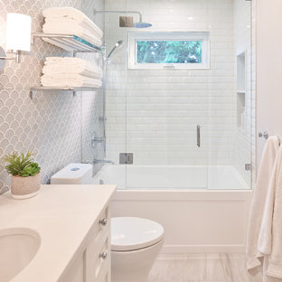 На фото: маленькая детская ванная комната в стиле современная классика с фасадами в стиле шейкер, белыми фасадами, ванной в нише, душем над ванной, унитазом-моноблоком, серой плиткой, плиткой из листового стекла, серыми стенами, полом из керамогранита, врезной раковиной, столешницей из искусственного кварца, серым полом, душем с распашными дверями и белой столешницей с