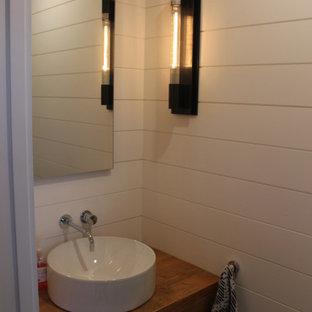 Klassisk inredning av ett litet badrum för barn, med öppna hyllor, skåp i slitet trä, en toalettstol med hel cisternkåpa, keramikplattor, vita väggar, skiffergolv, ett konsol handfat, träbänkskiva och grått golv