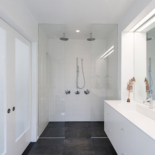 Inspiration for a large modern master white tile porcelain floor and black floor bathroom remodel in DC Metro with flat-panel cabinets, white cabinets, white walls, a trough sink and solid surface countertops