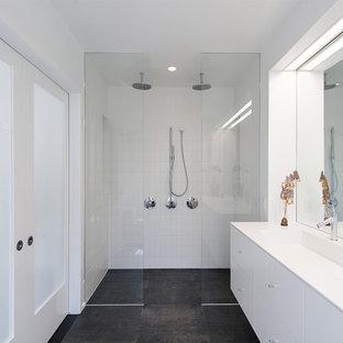 Стильный дизайн: большая главная ванная комната в стиле модернизм с плоскими фасадами, белыми фасадами, белыми стенами, полом из керамогранита, раковиной с несколькими смесителями, столешницей из искусственного камня, черным полом, открытым душем, двойным душем и белой плиткой - последний тренд