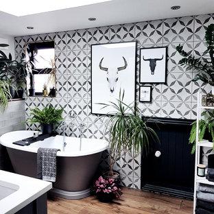 Scandi ensuite bathroom with a freestanding bath, black and white tiles, grey tiles, medium hardwood flooring and brown floors.