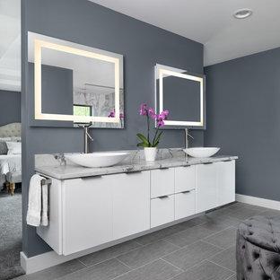 Foto på ett stort vintage grå en-suite badrum, med släta luckor, vita skåp, grå kakel, grå väggar, ett fristående handfat och grått golv