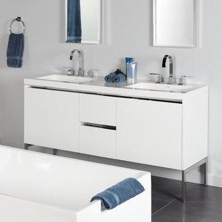 Cette image montre une grand salle de bain principale minimaliste avec un placard en trompe-l'oeil, des portes de placard blanches, une baignoire indépendante, un mur bleu, un sol en carrelage de céramique, un lavabo posé, un plan de toilette en surface solide et un sol turquoise.