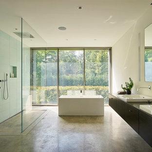 Esempio di una stanza da bagno moderna con ante lisce, ante in legno bruno, vasca freestanding, piastrelle blu, piastrelle di vetro, pareti bianche, pavimento in cemento, lavabo da incasso, pavimento grigio e top marrone