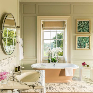 Photo of a large classic bathroom in Other with a freestanding bath, green walls, marble flooring, a console sink and white floors.