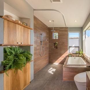 Ejemplo de cuarto de baño principal, contemporáneo, de tamaño medio, con ducha con cortina, puertas de armario de madera oscura, bañera encastrada, ducha a ras de suelo, paredes grises, suelo de baldosas de porcelana y suelo gris