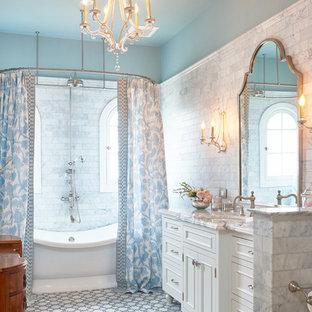 Immagine di una stanza da bagno padronale classica con consolle stile comò, ante bianche, vasca freestanding, piastrelle grigie, piastrelle in pietra, pareti blu, pavimento con piastrelle a mosaico, lavabo sottopiano, top in marmo, vasca/doccia e doccia con tenda