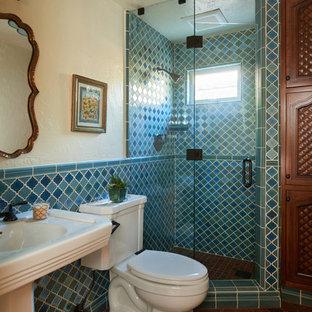 Modelo de cuarto de baño mediterráneo con lavabo con pedestal, baldosas y/o azulejos azules, ducha esquinera, suelo de baldosas de terracota, sanitario de dos piezas y paredes amarillas