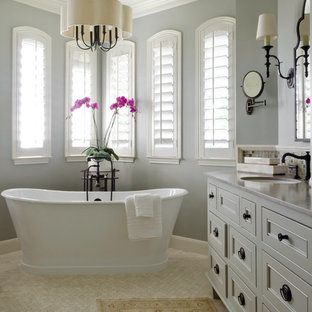 Design ideas for a mid-sized traditional master bathroom in Austin with an undermount sink, furniture-like cabinets, grey cabinets, limestone benchtops, a freestanding tub, a corner shower, white tile, stone tile, blue walls and travertine floors.
