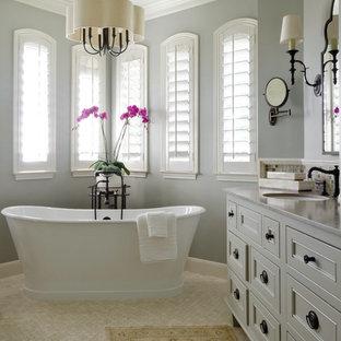 Idee per una stanza da bagno padronale classica di medie dimensioni con lavabo sottopiano, consolle stile comò, ante grigie, top in pietra calcarea, vasca freestanding, doccia ad angolo, piastrelle bianche, piastrelle in pietra, pareti blu e pavimento in travertino