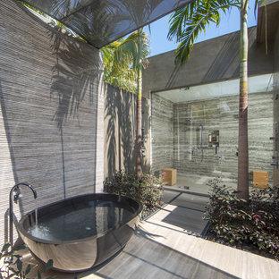 Пример оригинального дизайна: огромная главная ванная комната в морском стиле с отдельно стоящей ванной, душевой комнатой, серой плиткой, серыми стенами, бежевым полом и душем с распашными дверями