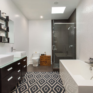 Photo of a medium sized contemporary ensuite bathroom in Los Angeles with dark wood cabinets, a freestanding bath, a corner shower, a one-piece toilet, white tiles, black tiles, white walls, ceramic flooring, a wall-mounted sink, glass worktops, brown floors, a hinged door, flat-panel cabinets and green worktops.
