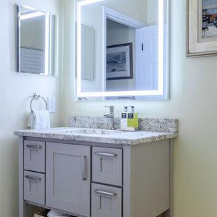 Esempio di una piccola stanza da bagno con doccia tradizionale con ante in stile shaker, ante grigie, vasca da incasso, vasca/doccia, WC monopezzo, piastrelle bianche, piastrelle in ceramica, pareti gialle, pavimento in bambù, lavabo sottopiano, top in granito, pavimento marrone, porta doccia scorrevole, top beige, un lavabo e mobile bagno freestanding