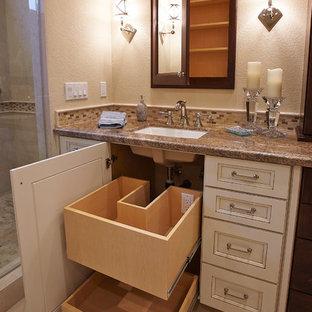 Пример оригинального дизайна: большая главная ванная комната в классическом стиле с фасадами с выступающей филенкой, белыми фасадами, полновстраиваемой ванной, душем в нише, бежевой плиткой, коричневой плиткой, стеклянной плиткой, бежевыми стенами, полом из керамогранита, врезной раковиной, столешницей из гранита, бежевым полом и душем с распашными дверями