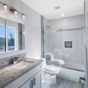 Example of a mid-sized trendy 3/4 gray tile and mosaic tile medium tone wood floor and gray floor bathroom design in Los Angeles with shaker cabinets, white cabinets, a one-piece toilet, white walls, an undermount sink and granite countertops