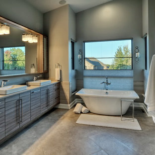Inspiration for a large 1950s master porcelain tile and beige tile porcelain floor and gray floor bathroom remodel in Omaha with flat-panel cabinets, gray cabinets, blue walls, a drop-in sink, solid surface countertops, a hinged shower door and beige countertops