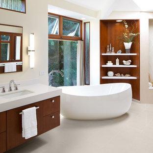 Foto på ett stort vintage en-suite badrum, med släta luckor, skåp i mellenmörkt trä, ett fristående badkar, en kantlös dusch, beige kakel, beige väggar, klinkergolv i keramik, ett undermonterad handfat, bänkskiva i kvartsit och en toalettstol med separat cisternkåpa