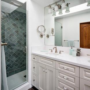 サンフランシスコの中サイズのビーチスタイルのおしゃれなマスターバスルーム (アンダーカウンター洗面器、白いキャビネット、珪岩の洗面台、アルコーブ型シャワー、青いタイル、セラミックタイル、白い壁、磁器タイルの床、レイズドパネル扉のキャビネット、分離型トイレ) の写真