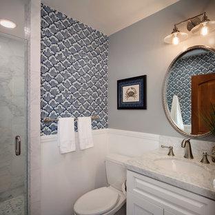 Ispirazione per una piccola stanza da bagno con doccia costiera con lavabo sottopiano, ante con bugna sagomata, ante bianche, top in marmo, doccia alcova, WC a due pezzi, piastrelle bianche, piastrelle in pietra e pareti multicolore