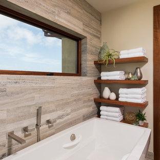 Réalisation d'une salle de bain principale minimaliste de taille moyenne avec un placard à porte plane, des portes de placard marrons, une baignoire indépendante, une douche à l'italienne, un carrelage vert, du carrelage en pierre calcaire, un sol en calcaire, un lavabo encastré et un plan de toilette en calcaire.