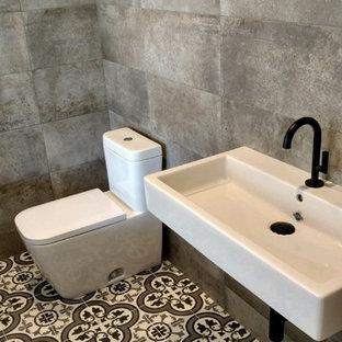Свежая идея для дизайна: ванная комната среднего размера в стиле лофт с унитазом-моноблоком, серыми стенами, полом из керамической плитки, подвесной раковиной, фасадами в стиле шейкер, искусственно-состаренными фасадами, серой плиткой, цементной плиткой, душевой кабиной и разноцветным полом - отличное фото интерьера
