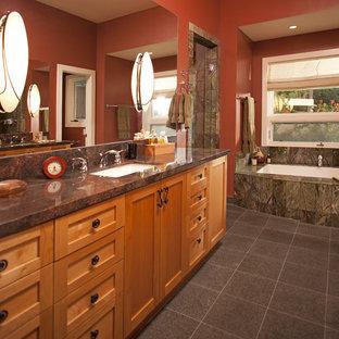 サンディエゴの大きいエクレクティックスタイルのおしゃれなマスターバスルーム (シェーカースタイル扉のキャビネット、中間色木目調キャビネット、アンダーマウント型浴槽、アルコーブ型シャワー、一体型トイレ、茶色いタイル、磁器タイル、赤い壁、磁器タイルの床、アンダーカウンター洗面器、御影石の洗面台) の写真