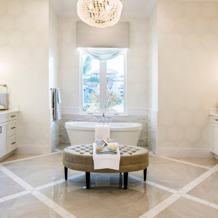 Modelo de cuarto de baño principal, marinero, grande, con armarios con paneles empotrados, puertas de armario blancas, bañera exenta, ducha abierta, sanitario de una pieza, baldosas y/o azulejos con efecto espejo, paredes beige, suelo de mármol, lavabo encastrado, encimera de granito, suelo beige, ducha abierta y encimeras blancas