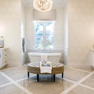 Ispirazione per una grande stanza da bagno padronale costiera con ante con riquadro incassato, ante bianche, vasca freestanding, doccia aperta, WC monopezzo, piastrelle a specchio, pareti beige, pavimento in marmo, lavabo da incasso, top in granito, pavimento beige, doccia aperta e top bianco