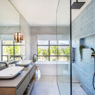 Contemporary bathroom in Melbourne with flat-panel cabinets, medium wood cabinets, a freestanding tub, blue tile, a vessel sink, grey floor and grey benchtops.