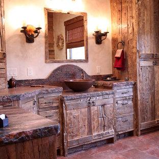 Ejemplo de cuarto de baño principal, rústico, grande, con lavabo sobreencimera, armarios con paneles lisos, puertas de armario con efecto envejecido, encimera de granito, bañera exenta, baldosas y/o azulejos rojos, baldosas y/o azulejos de piedra, paredes beige y suelo de pizarra