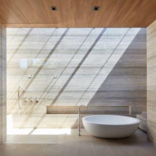На фото: класса люкс большие главные ванные комнаты в стиле модернизм с отдельно стоящей ванной, плиткой из травертина, полом из известняка, бежевым полом, открытым душем, душем без бортиков, серой плиткой и серыми стенами