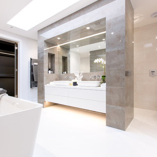 Photo of a large contemporary ensuite bathroom in Dorset with a freestanding bath, brown tiles, porcelain flooring, white floors, flat-panel cabinets, white cabinets, a vessel sink, a hinged door and white walls.