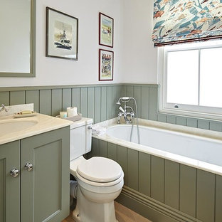Inspiration for a small traditional family bathroom in London with recessed-panel cabinets, green cabinets, an alcove bath, a shower/bath combination, a one-piece toilet, multi-coloured tiles, beige walls, a submerged sink, marble worktops, brown floors and an open shower.