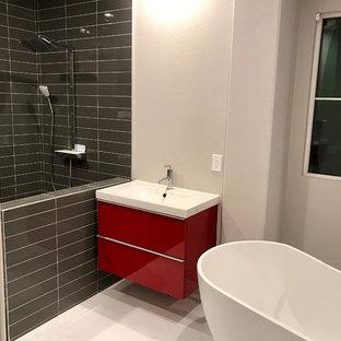 Idee per una stanza da bagno padronale design di medie dimensioni con ante lisce, ante rosse, vasca freestanding, doccia aperta, piastrelle grigie, piastrelle in gres porcellanato, pareti bianche, pavimento in marmo, lavabo integrato, top in superficie solida, pavimento bianco e doccia aperta