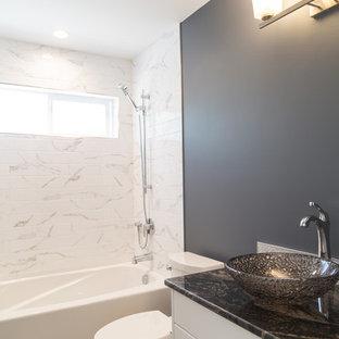 他の地域の中サイズのおしゃれな浴室 (シェーカースタイル扉のキャビネット、白いキャビネット、ドロップイン型浴槽、シャワー付き浴槽、分離型トイレ、白いタイル、セラミックタイル、黒い壁、セラミックタイルの床、ベッセル式洗面器、珪岩の洗面台、グレーの床、シャワーカーテン、黒い洗面カウンター) の写真