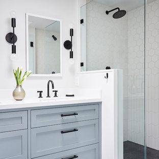 Réalisation d'une salle de bain principale tradition avec un placard à porte shaker, des portes de placard bleues, une douche double, un carrelage blanc, des carreaux de céramique, un mur blanc, un sol en carrelage de céramique, un lavabo encastré, un plan de toilette en quartz modifié, un sol gris, une cabine de douche à porte battante et un plan de toilette blanc.