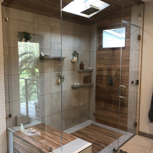 Photo of a medium sized world-inspired ensuite bathroom in San Francisco with recessed-panel cabinets, brown cabinets, a corner shower, a two-piece toilet, beige tiles, ceramic tiles, beige walls, ceramic flooring, a built-in sink, quartz worktops, multi-coloured floors, a hinged door, grey worktops, a shower bench, a single sink, a floating vanity unit, a vaulted ceiling and wallpapered walls.