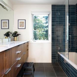 Imagen de cuarto de baño vintage con armarios con paneles lisos, puertas de armario de madera oscura, bañera esquinera, combinación de ducha y bañera, baldosas y/o azulejos azules, paredes blancas, lavabo bajoencimera, suelo negro, ducha abierta y encimeras blancas