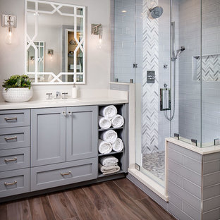 Classic ensuite bathroom in San Diego with grey cabinets, a freestanding bath, grey tiles, metro tiles, grey walls, medium hardwood flooring, a corner shower, a submerged sink and a hinged door.