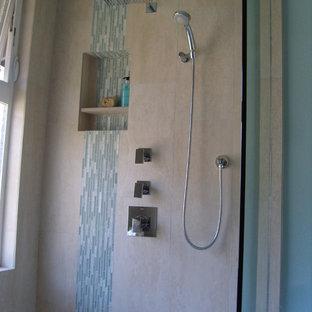 Modelo de cuarto de baño principal, tropical, pequeño, con lavabo bajoencimera, armarios con paneles lisos, puertas de armario de madera oscura, encimera de cuarzo compacto, ducha empotrada, sanitario de dos piezas, baldosas y/o azulejos beige, baldosas y/o azulejos de porcelana, paredes azules y suelo de baldosas de porcelana