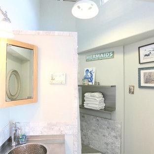 Ispirazione per una stanza da bagno costiera di medie dimensioni con ante in legno chiaro, piastrelle grigie, piastrelle bianche, piastrelle in pietra, pavimento in gres porcellanato, lavabo da incasso e top in acciaio inossidabile