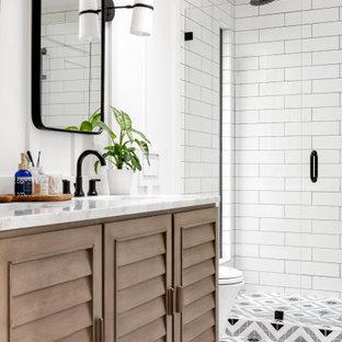 Bild på ett maritimt vit vitt badrum, med luckor med lamellpanel, skåp i mellenmörkt trä, en dusch i en alkov, vit kakel, tunnelbanekakel, vita väggar, ett undermonterad handfat, flerfärgat golv och dusch med gångjärnsdörr
