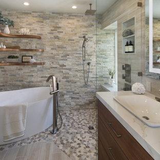 Inspiration för moderna beige en-suite badrum, med släta luckor, skåp i mellenmörkt trä, ett fristående badkar, en kantlös dusch, beige kakel, porslinskakel, beige väggar, klinkergolv i småsten, ett fristående handfat, bänkskiva i kvarts, flerfärgat golv och med dusch som är öppen