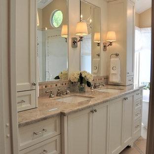 オレンジカウンティの中サイズのトラディショナルスタイルのおしゃれなマスターバスルーム (落し込みパネル扉のキャビネット、白いキャビネット、置き型浴槽、コーナー設置型シャワー、一体型トイレ、白いタイル、磁器タイル、ベージュの壁、ライムストーンの床、アンダーカウンター洗面器、珪岩の洗面台、ベージュの床、開き戸のシャワー) の写真