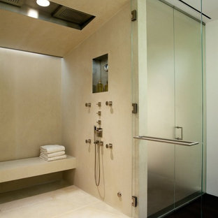 Example of a minimalist beige tile and limestone tile alcove shower design in New York