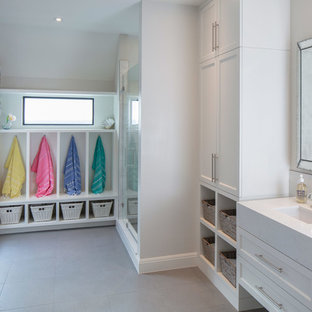 Inspiration for a mid-sized contemporary gray floor alcove shower remodel in Austin with recessed-panel cabinets, white cabinets, engineered quartz countertops, a hinged shower door, white countertops, gray walls and an undermount sink