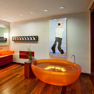 На фото: большие главные ванные комнаты в стиле фьюжн с отдельно стоящей ванной, бежевыми стенами, темным паркетным полом, раковиной с несколькими смесителями, коричневым полом и оранжевой столешницей