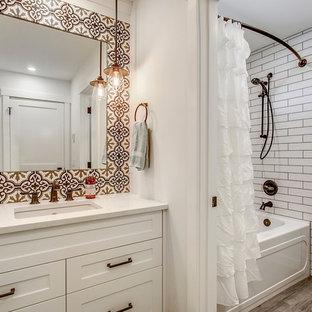 Bild på ett mellanstort vintage en-suite badrum, med skåp i shakerstil, vita skåp, ett badkar i en alkov, en toalettstol med separat cisternkåpa, vit kakel, cementkakel, vinylgolv, ett undermonterad handfat, bänkskiva i kvartsit, grått golv, en dusch/badkar-kombination, vita väggar och dusch med duschdraperi